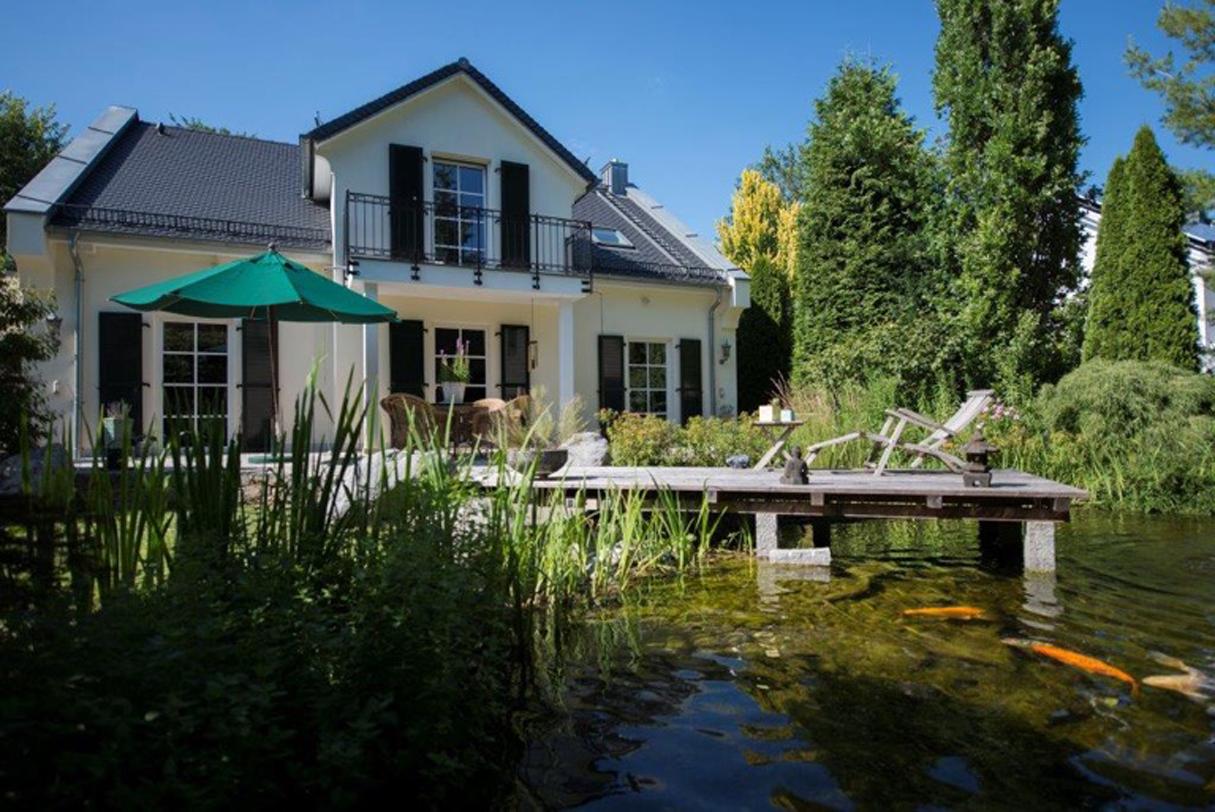 Landhaus im englischen Stil mit Teich im Garten
